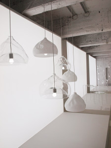 *照明製品やテーブルなどが照明付きの白いパネルを背景に展示されています